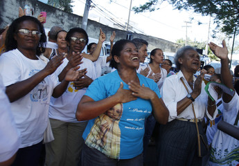 Faithfuls react during the visit of the World Youth Day symbols at the Vidigal slum in Rio de Janeiro