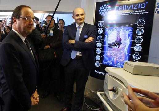 French President Hollande and Mauna Kea Technologies CEO Loiseau listen to the presentation of Cellvizio, a Medical Endomicroscopy virtual assistant at Mauna Kea Technologies office in Paris