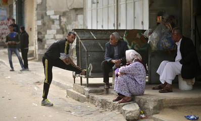 Palestinian Olympic runner Nader Al-Masri stretches near his house in Beit Hanoun in the northern Gaza Strip