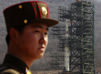A soldier stands guard in front of the Unha-3 (Milky Way 3) rocket sitting on a launch pad at the West Sea Satellite Launch Site, during a guided media tour by North Korean authorities in the northwest of Pyongyang