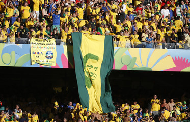 Brazil fans celebrate with a picture of soccer legend Pele at the end of the 2014 World Cup round of 16 game between Brazil and Chile at the Mineirao stadium