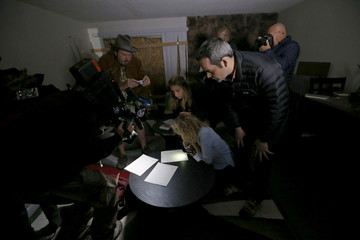 News media look at documents left inside the home of suspects Syed Rizwan Farook and Tashfeen Malik in Redlands, California