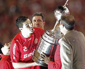 Bolivar of Internacional receives the trophy from Pele after defeating Guadalajara Chivas in the final match of the Copa Libertadores in Porto Alegre