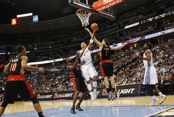 Denver Nuggets forward Martin drives to the basket past Toronto Raptors players during their NBA basketball game in Denver