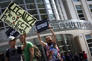 Demonstrators hold signs as they protest the arrests of male escort service Rentboy.com staffers outside United States Court in the Brooklyn borough of New York