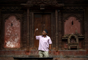 "A man takes a picture of a parade during the Gaijatra festival, also known as ""cow festival,"" in Kathmandu"