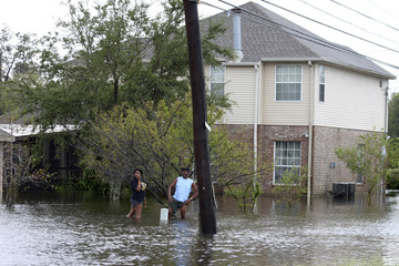 The  McCoys stand in the back yard of their flooded home during the aftermath of Hurricane Isaac near Airline Highway in Reserve, Louisiana