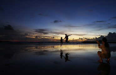 A woman takes pictures of her husband and child during sunset in Kuta beach, Bali resort island