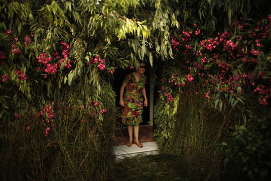 A woman leaves her house through a decorated doorway during Corpus Christi day in Zahara de la Sierra