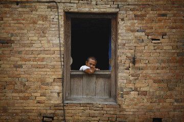 A man falls asleep while he sits at the window of his house in Lalitpur