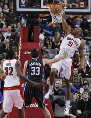 Raptors' Magloire goes up for a slam dunk with teammate Davis against Magic's Anderson during their NBA basketball game in Toronto