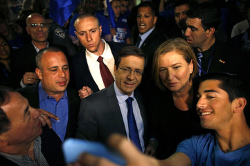 Herzog and Livni, co-leaders of the center-left Zionist Union party, campaign outside a polling station in Modiin