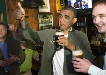 Obama gives a thumbs-up as he celebrates St. Patrick's Day with a pint of Guinness during a stop at the Dubliner Irish pub in Washington