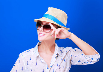 Portrait of beautiful model in hat with glasses ,isolated on blue background