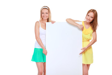 Two young pretty women with empty board for the text on a white background