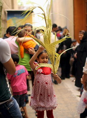 An Egyptian Coptic Christian girl carries a palm decoration during Palm Sunday inside a church in Old Cairo