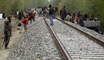 An Indian army soldier stands guard as workers repair the embankment of a railway track after a blast in Kakpora