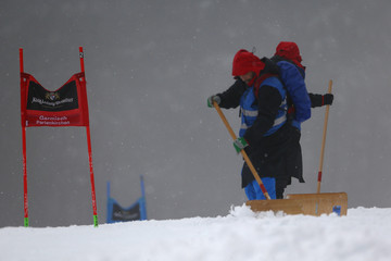 Workers shovel snow on the course for the World Cup Men's giant slalom race in the Bavarian ski resort of Garmisch-Partenkirchen