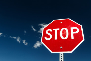 Stop sign against bright blue sky.