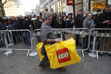 People queue outside the world's biggest Lego store in Leicester Square in London