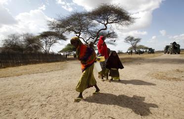 Somali women carry relief food from the Kenya Defence Force in Tabda village near the Kenya-Somalia border