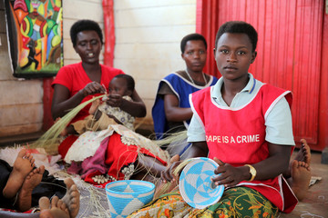 Burundian refugee women weave traditional baskets as they listen to Pakistani Nobel Peace Prize laureate Malala at the Mahama refugee camp, Rwanda