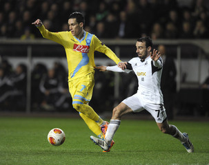Swansea City's Leon Britton challenges Napoli's Jose Callejon during their Europa League soccer match at the Liberty Stadium in Swansea,
