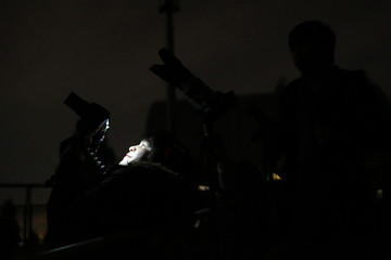 A woman points her camera while waiting for a total lunar eclipse in Oakland, California