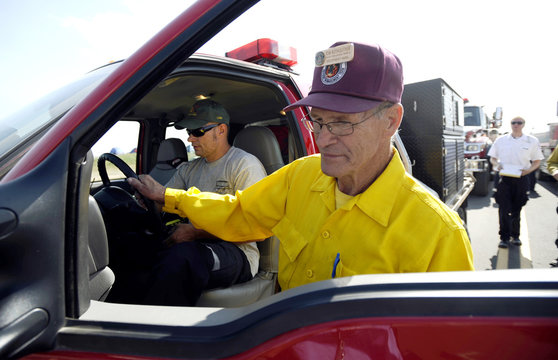 Ruthleutner inspects the South Metro brush fire truck while Spader turns on all the lights at the staging area near Boulder reservoir prior to going to the Fourmile Canyon fire in Boulder