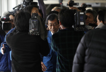 Tokyo Electric Power Co President Shimizu is mobbed by media upon his arrival for a meeting with Japan's Vice Trade Minister Ikeda in Fukushima