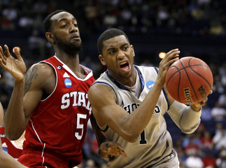 Georgetown University's Thompson is pressured by North Carolina State University's Leslie during their men's NCAA college basketball game in Columbus