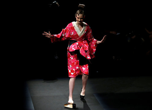 A model struggles with a shoe as she presents a creation by designer Yoshiki from his Spring/Summer 2017 collection for his brand YOSHIKIMONO during Tokyo Fashion Week in Tokyo