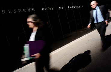 Pedestrians walk past the Reserve Bank of Australia Building in Sydney's central business district