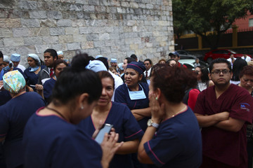 Employees wait outside a private hospital after a 6.8 magnitude earthquake in Mexico City