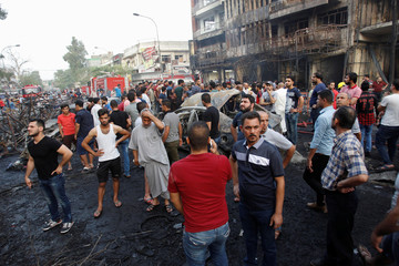 People gather at the site of a suicide car bomb in the Karrada shopping area, in Baghdad, Iraq