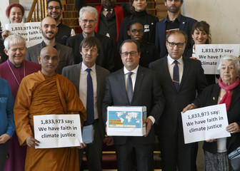 France's President Francois Hollande (C) holds a box containing an international petition to support the climate talks as he poses with religious figures for a group photo at the Elysee Palace in Paris