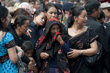 Mourners react as the repatriation cortege of four soldiers passes through Wootton Bassett