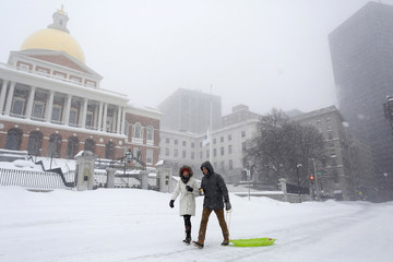 Two people pull a sled down Beacon Street during a blizzard in Boston
