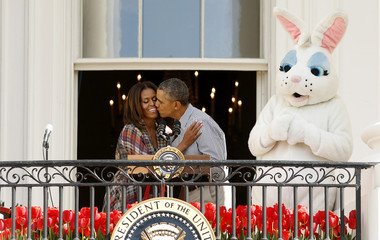 Obama kisses Michelle Obama next to the Easter Bunny during the 136th annual Easter Egg Roll on the South Lawn of the White House in Washington