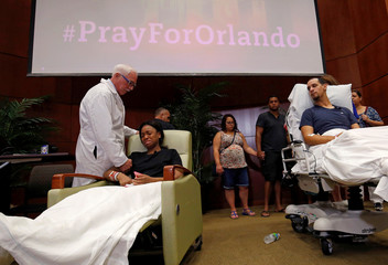 Gunshot survivor Patience Carter is comforted by Dr. Neil Finkler as fellow survivor Angel Santiago looks on at a news conference at Florida Hospital Orlando on the shooting at the Pulse gay nightclub in Orlando