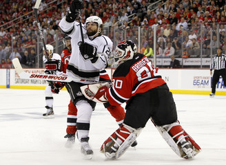 New Jersey Devils goalie Brodeur comes out to clear a puck as he collides with Los Angeles Kings' Stoll in the first period during Game 5 of the NHL Stanley Cup hockey final in Newark