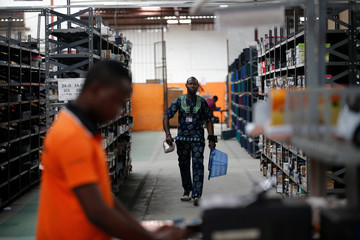 A man walks past shelves with branded packets as he holds a basket at a warehouse for an online store, Jumia in Ikeja district in Lagos