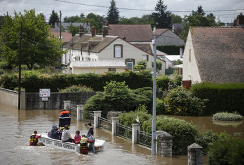 French firefighters on a small boat evacuate residents from a flooded area after heavy rain falls in Chalette-sur-Loing, near Orleans