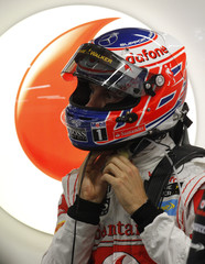 McLaren Formula One driver Button adjusts his helmet during the second practice session of the Singapore F1 Grand Prix at the Marina Bay street circuit in Singapore