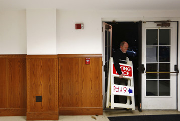 A poll worker carries voting place signs after the polls closed at the Covenant Presbyterian Church during the U.S. presidential election in Charlotte, North Carolina