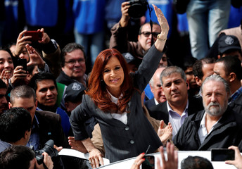 Former Argentine President Fernandez de Kirchner waves to supporters as she leaves a Justice building