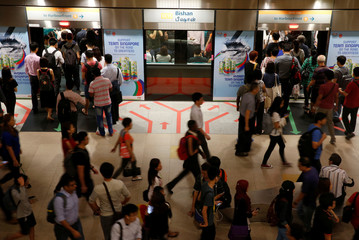 People get on board an SMRT train during morning rush hour in Singapore