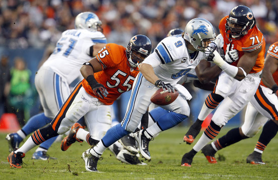 Lions quarterback Stafford is chased down by Bears Briggs and Idonije in the first half of their NFL football game in Chicago