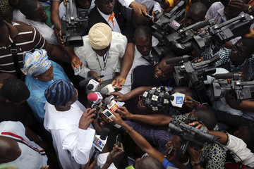Osun state governor and candidate for All Progressive Congress (APC) Ogbeni Rauf Aregbesola stands in the crowd as journalists interview him at the start of the Osun state governorship election in Ifofin village in Ilesa