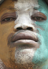 A man with his face painted in the colours of the Ivory Coast flag is seen as supporters of Laurent Gbagbo take part in a demonstration in Abidjan